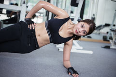 Beautiful muscular fit woman exercising building muscles and fit. Ness woman doing exercises in the gym. Fitness - concept of healthy lifestyle,soft focus Stock Photography