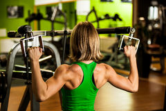 Beautiful muscular fit woman exercising building muscles in fitn Royalty Free Stock Image