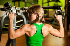 Beautiful muscular fit woman exercising building muscles in fitn Stock Photos