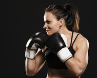 Female fighter ready to fight. Beautiful muscular fitness woman wearing boxing gloves Royalty Free Stock Photo