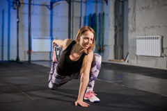 Beautiful muscular girl in gray leggings doing stretching. Sports gym in industrial style royalty free stock photos