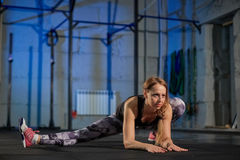 Beautiful muscular girl in gray leggings doing stretching. Sports gym in industrial style royalty free stock photography