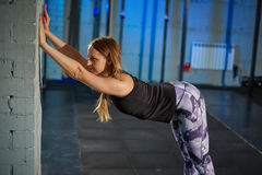 Beautiful muscular girl in gray leggings doing stretching. Sports gym in industrial style royalty free stock images