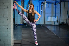 Beautiful muscular girl in gray leggings doing stretching. Sports gym in industrial style stock photo