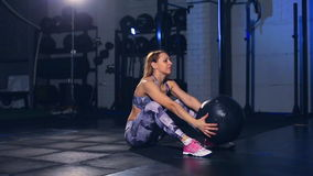 Beautiful muscular girl in gray tight tights sit ups with medicine ball throw. Cross fit. Beautiful muscular girl in gray tight tights sit ups with medicine ball stock footage