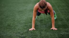 A beautiful muscular girl in leggings and a vest makes a burpee at the stadium. Crossfit, fitness, healthy lifestyle