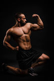 A beautiful, muscular man on a black background. A bodybuilder is posing in a studio. Sports concept. royalty free stock photos
