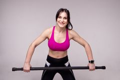 Beautiful muscular woman doing exercise with gymnastic stick on a gray background. stock photo
