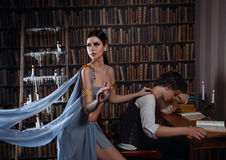 Beautiful Muse and the poor poet. Luxurious brunette in sexy Greco-Roman clothing,  she put his hand on the shoulder of the young man. The poet sad his head Royalty Free Stock Images