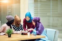 Beautiful Muslim and Arabic girls reading Koran together in group. stock photo