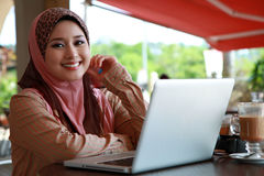Beautiful Muslim Girl. Using Laptop and smile to the camera Royalty Free Stock Photos