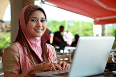 Beautiful Muslim Girl. Using Laptop and smile to the camera stock photography