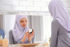 Beautiful Muslim girl with acne problem using cream. While looking in mirror indoors Royalty Free Stock Photo