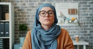 Muslim girl in hijab putting on glasses and looking at camera in office. Beautiful Muslim girl in hijab is putting on trendy glasses and looking at camera with stock video