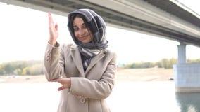 Beautiful Muslim girl raising hand. Outdoor stock footage
