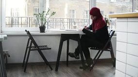 Beautiful muslim girl wearing hijab is looking for something on the internet in her laptop and writes something down. While sitting in a minimalistic light stock video footage