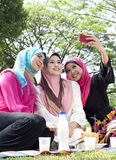 Beautiful Muslim girlfriends taking picture. By phone in the park Royalty Free Stock Photos