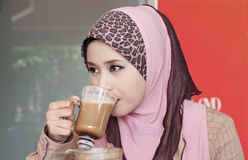 Beautiful muslim woman and coffee. Beautiful muslim woman drink coffee at cafe royalty free stock photography