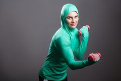 Beautiful muslim woman in green hijab or islamic sportswear stan. Ding, holding red dumbbells training biceps, looking at camera with toothy smile. indoor studio royalty free stock photos