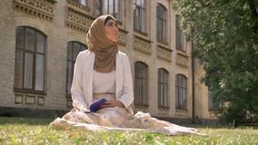 Beautiful muslim woman in hijab sitting on grass in park and reading book, looking around, building in background.  stock video footage