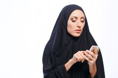 Beautiful Muslim woman holding a cellphone Stock Image