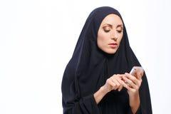 Beautiful Muslim woman holding a cellphone Stock Image