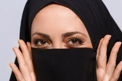 Beautiful Muslim woman looking at camera. Her beauty lies in her eyes. Closeup image of beautiful young Muslim woman in chador covering her face with  dark cloth Royalty Free Stock Image