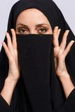Beautiful Muslim woman looking at camera. Her beauty lies in her eyes. Closeup image of beautiful young Muslim woman in chador covering her face with  dark cloth Stock Photography