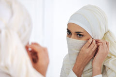 Beautiful Muslim woman looking at mirror Stock Photos