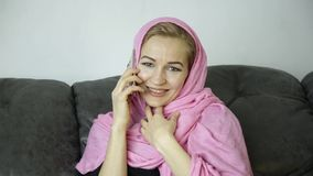 Beautiful muslim woman in pink hijab sitting on a sofa in a cafe and talking on cell phone. Beautiful arabian woman in pink hijab sitting on a sofa in a cafe and stock video footage