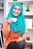 Beautiful muslim woman smiling while holding a cup of tea Royalty Free Stock Photo