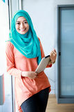 Beautiful muslim woman smiling while holding a tablet Royalty Free Stock Photo