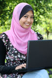 Beautiful muslim woman using laptop. While sitting relaxed on bench at summer park Stock Photo