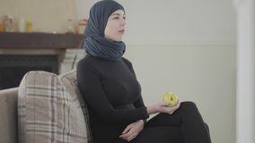 Beautiful muslim woman watching TV show and biting apple wearing traditional headscarf on the background of cozy living. Young beautiful muslim woman watching TV stock footage