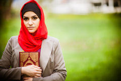 Beautiful muslim woman wearing hijab and holding a holy book Koran.