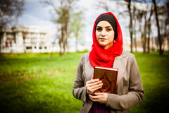 Beautiful muslim woman wearing hijab and holding a holy book Koran. Royalty Free Stock Photo