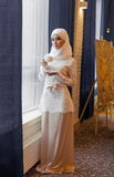 Beautiful Muslim woman in a white wedding dress standing at window. In hotel Royalty Free Stock Images
