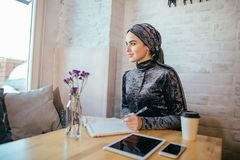 Muslim woman working in cafe stock photography