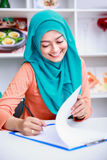 Beautiful muslim woman writing on paper Stock Photography