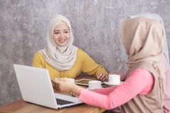 Beautiful muslim women explaining project on laptop to her partn. Portrait of beautiful muslim women explaining project on laptop to her partner at coffee shop Royalty Free Stock Images