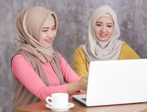 Beautiful muslim women presenting something on laptop to her sib. Close up portrait of beautiful muslim women presenting something on laptop to her sibling Royalty Free Stock Photos