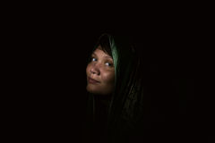 Beautiful Muslim young woman in darkness.  Dark room, the dim light of the flashlight Stock Photos