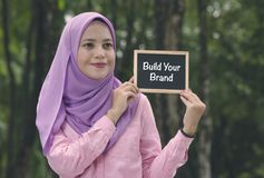 Beautiful muslimah stand and holding chalkboard with word BUILD YOUR BRAND. Conceptual image, shallow depth of field of beautiful muslimah stand and holding stock images