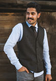 Beautiful mustache young man have fun outdoor. Handsome mustache young man wearing elegant clothes and posing outdoor at wooden background Royalty Free Stock Photos
