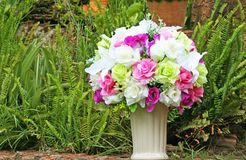 Beautiful muticolored artificial flowers in white vase. Close up Beautiful muticolored artificial flowers in white vase royalty free stock photo