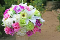 Beautiful muticolored artificial flowers in white vase. Close up Beautiful muticolored artificial flowers in white vase royalty free stock image