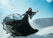 Beautiful mysterious Arab woman queen in black clothes. Girl fashion model posing, dancing in long, silk dress, fabric