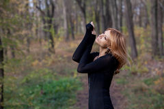 Beautiful mysterious blond woman in autumn forest Stock Photos