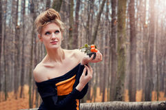 Beautiful mysterious girl in a dress in the autumn forest with tangerine trees Royalty Free Stock Images