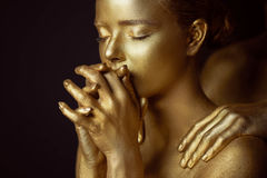 Beautiful mysterious girl, painted in gold color. Hands lips folded in prayer. On the shoulders of men`s hands.Status Stock Photo